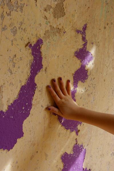 Lila Finger auf grauer Wand mit lila Farbe.